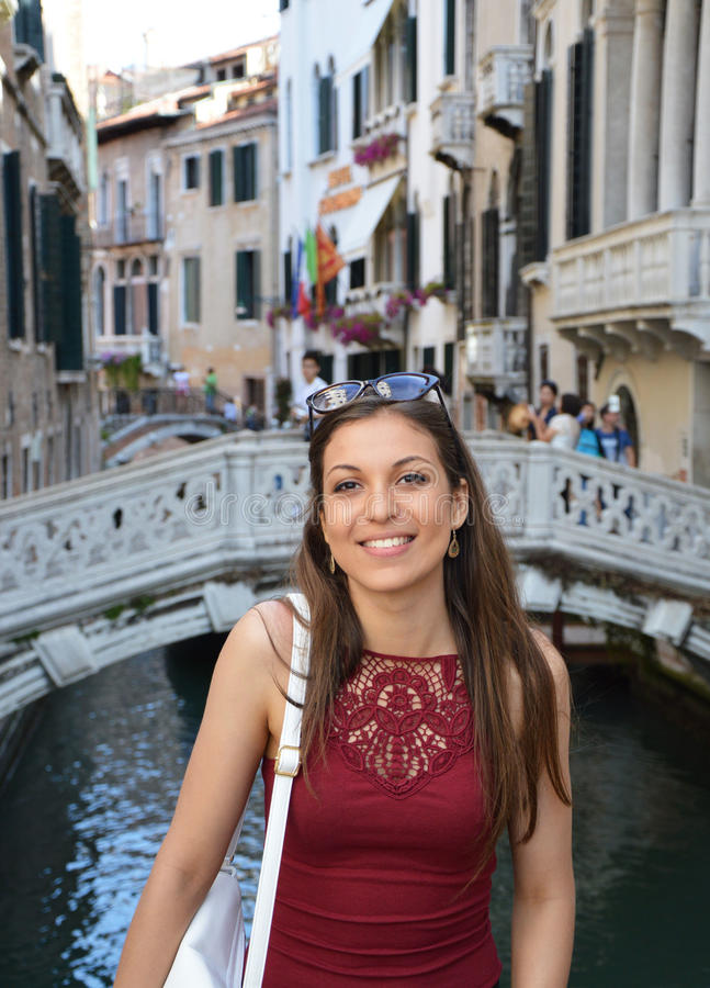 Smiling girl tourist standing above traditional bridge on canals in Venice. Beautiful woman model traveling in Venice, Italy royalty free stock photos