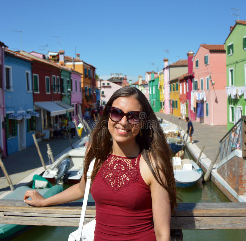 Smiling girl tourist with sunglasses, in a sunny day in Burano island, Venice. Beautiful woman model traveling in Venice, Italy stock photography
