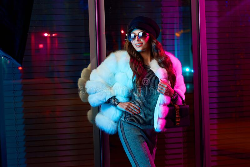 Smiling girl in trendy white fur coat and sunglasses stock photography