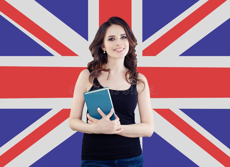 Smiling girl on the UK flag background. Pretty cheerful woman learning english language and traveling in United Kingdom royalty free stock image