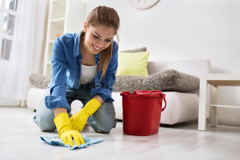 Smiling girl wash the floor with water stock photography