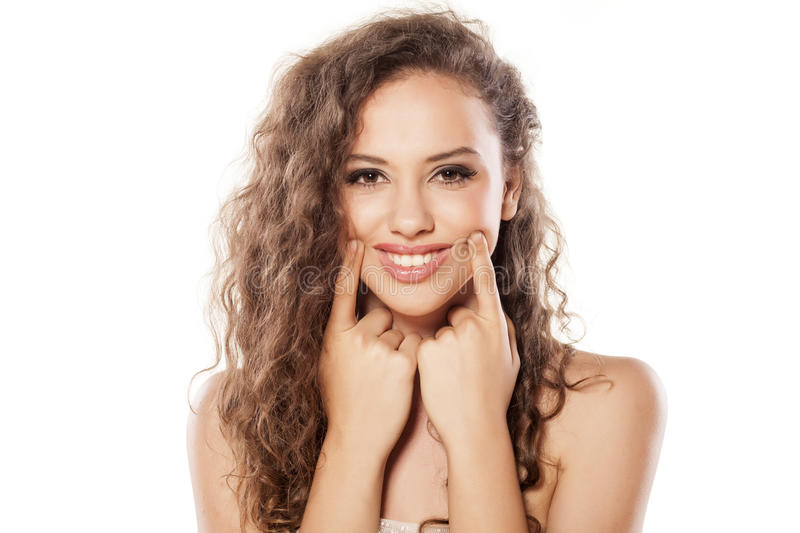Smiling girl. With wavy hair holding the edges of her lips with her fingers royalty free stock photo