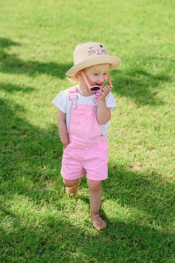 Smiling girl wearing pink sunglasses and walks on green lawn. The concept of summer vacation and carefree childhood. royalty free stock photos