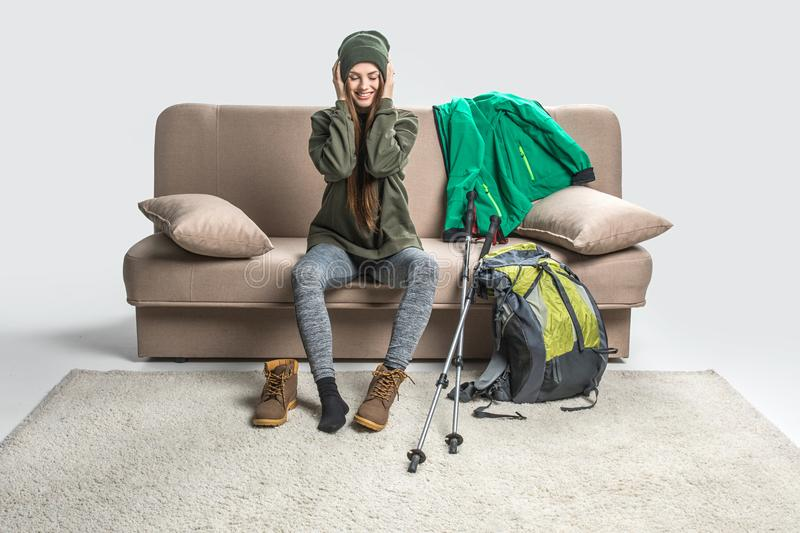 Smiling girl wearing warm clothing and hiking boots on sofa. With backpack stock photos