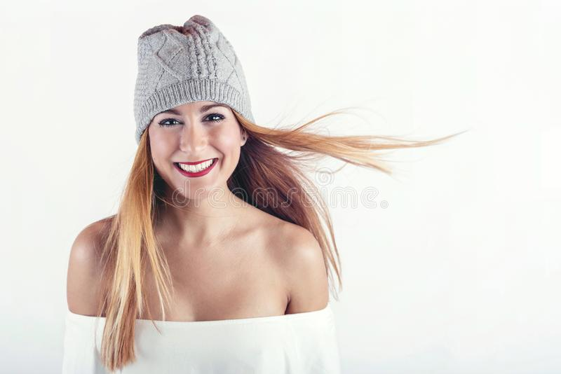 Smiling girl with winter hat. On white background stock photography