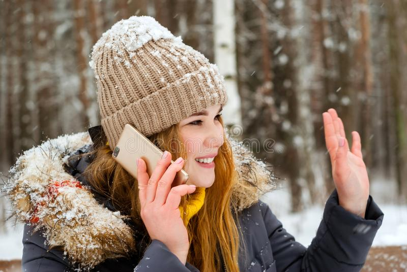 Girl greets someone by hand, talking on the phone in the winter in the open air royalty free stock images