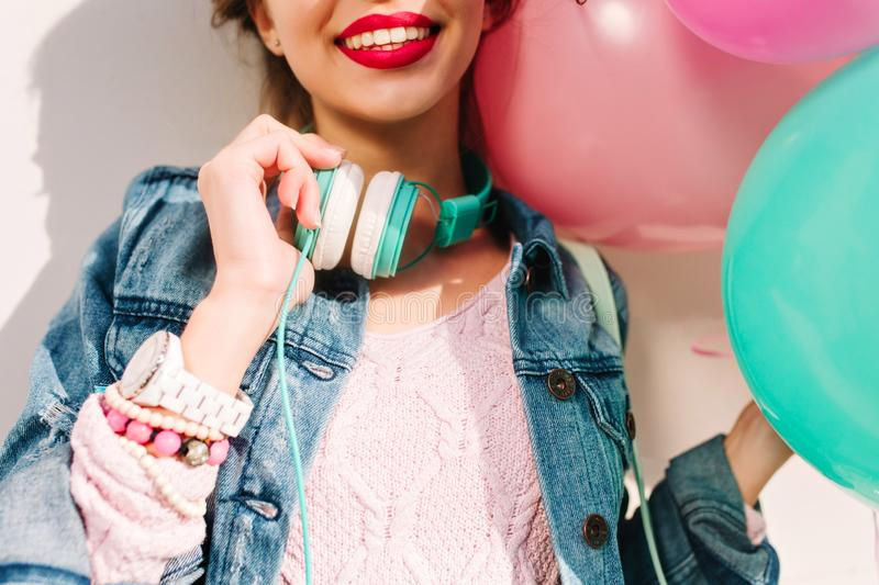 Smiling girl with wristwatch and cute handmade accessories holding new big turquoise headphones. Charming young woman stock photography