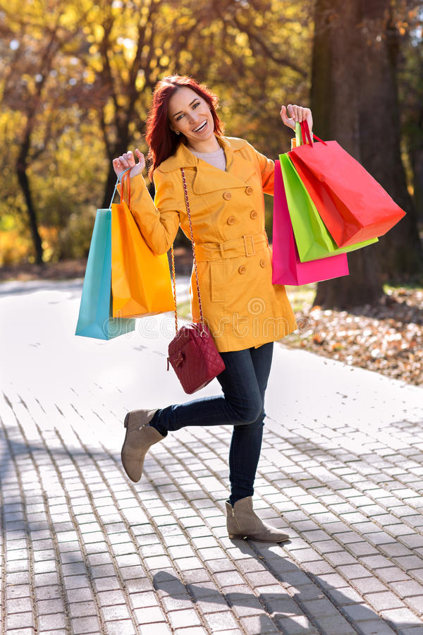 Smiling girl in yellow coat royalty free stock image
