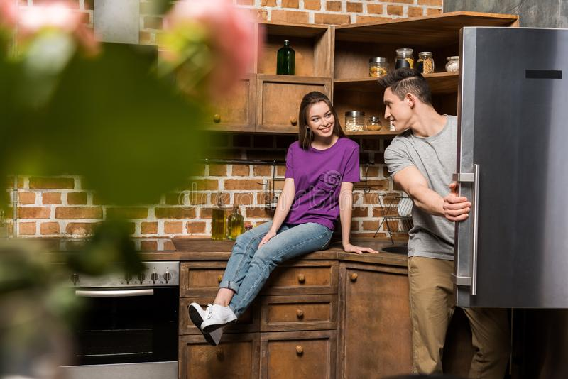 Smiling girlfriend looking at boyfriend opening. Fridge royalty free stock image