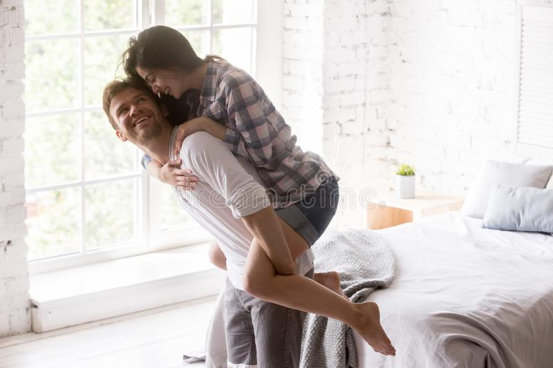 Smiling girlfriend piggyback boyfriend having fun at home. Excited young couple having fun at home, happy girl piggyback her boyfriend in white bedroom, strong stock images
