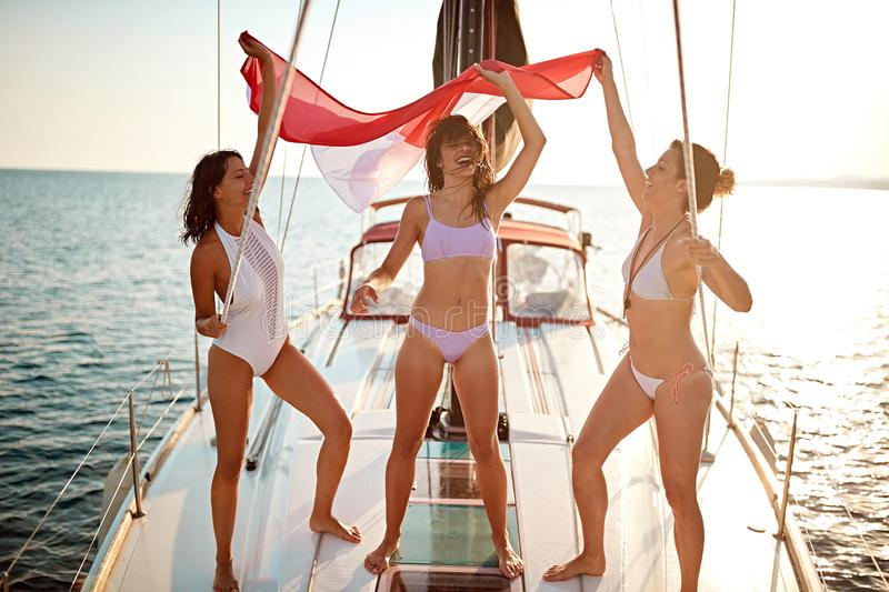 Girlfriends sailing on yacht and having party with flag royalty free stock images