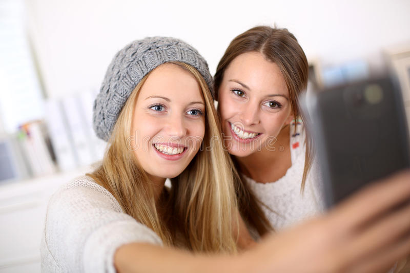 Smiling girlfriends taking selfie stock photography