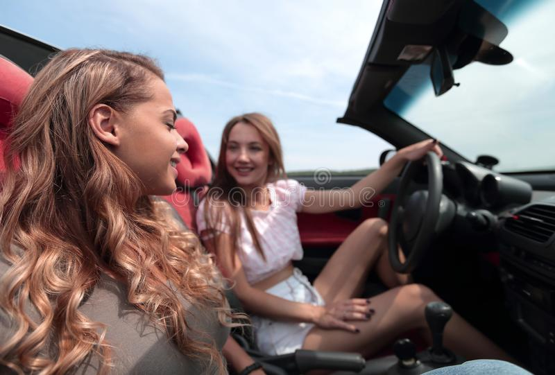 Smiling girlfriends traveling in a convertible car. stock photo
