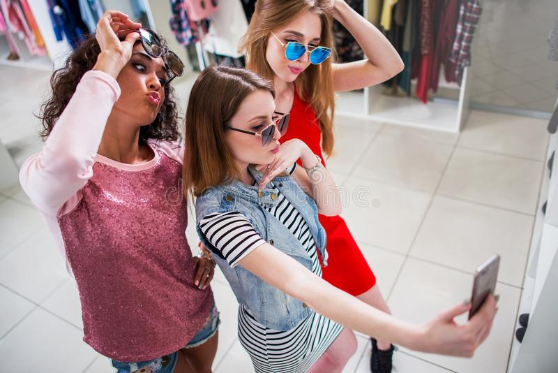 Smiling girlfriends wearing stylish sunglasses having fun time taking selfie with mobile phone while doing shopping in. Clothing store royalty free stock images