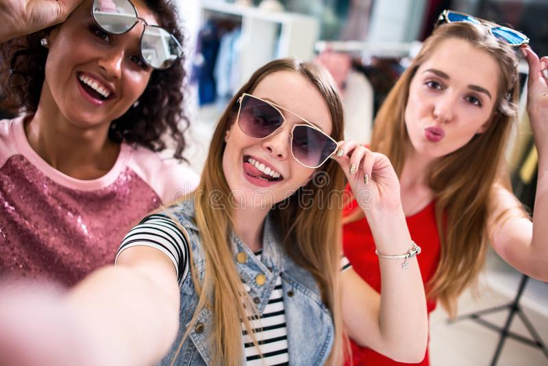 Smiling girlfriends wearing stylish sunglasses having fun time taking selfie with mobile phone while doing shopping in. Clothing store stock images