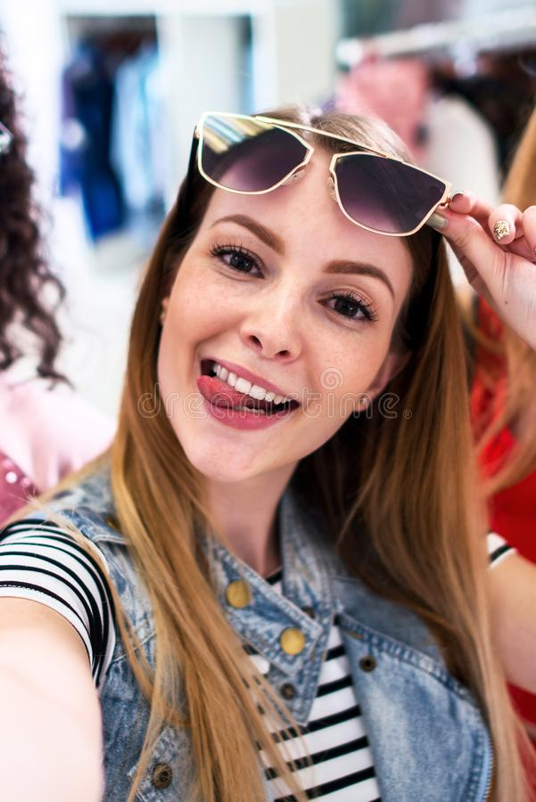 Smiling girlfriends wearing stylish sunglasses having fun time taking selfie with mobile phone while doing shopping in. Clothing store royalty free stock photography