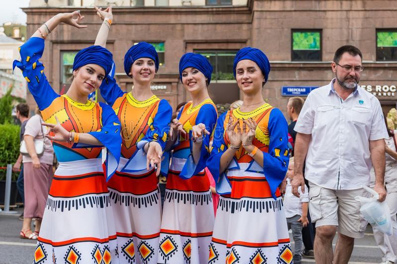 Smiling girls in beautiful national costumes posing on the street royalty free stock images