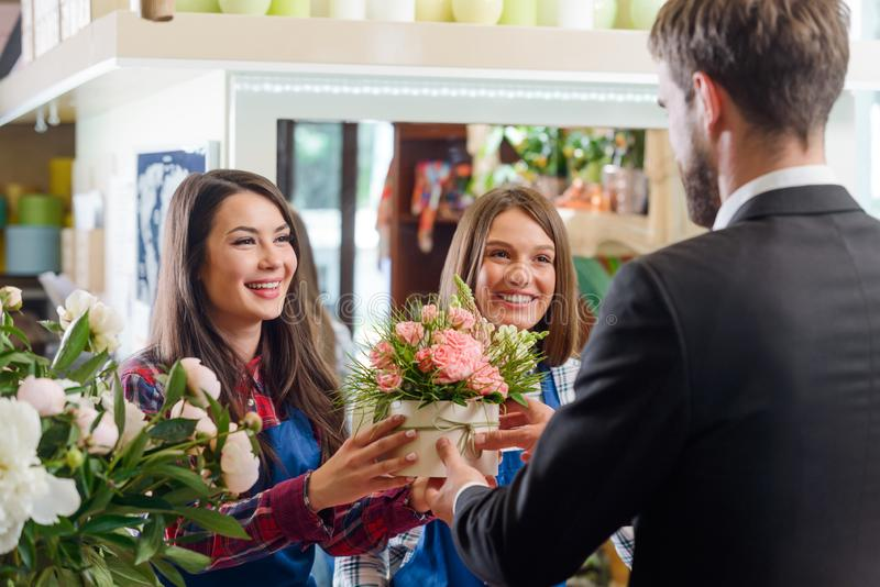 Smiling girls giving a bouquet royalty free stock photo