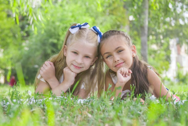 Smiling girls lying on green grass in the park in summer royalty free stock photo