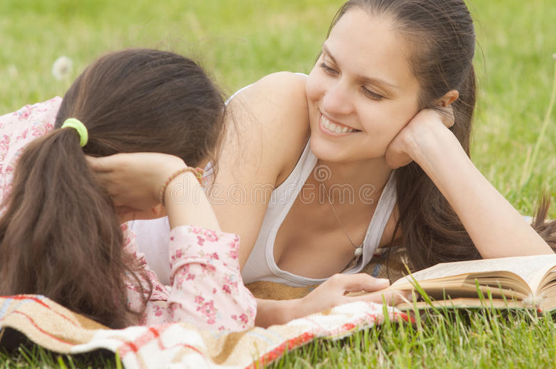 Smiling girls lying outdoor on the plaid stock photography