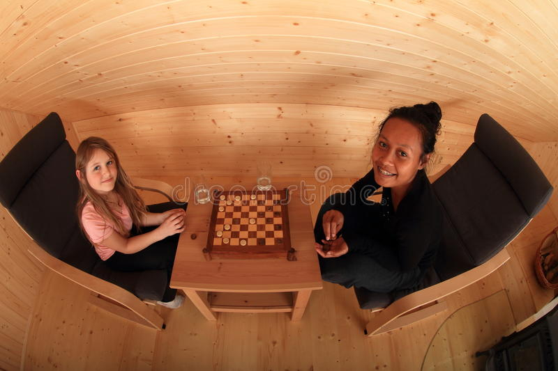 Smiling girls playing draughts. Two smiling girls sitting on armchairs - blond Caucasian kid and young exotic Papuan women playing draughts or checkers on stock photo