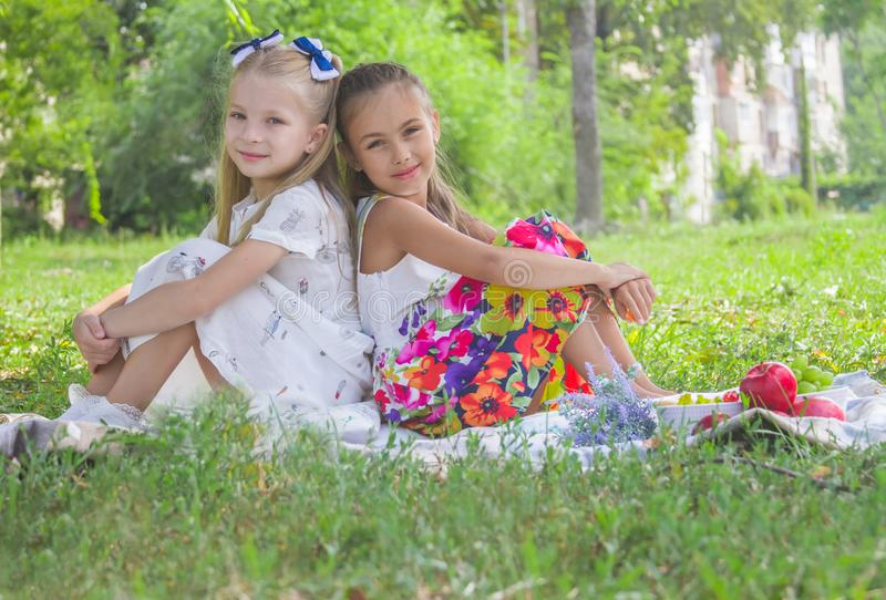 Smiling girls sitting back-to-back on green grass in the park in stock photography