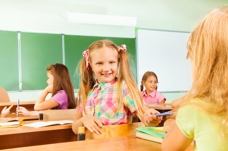 Smiling girls turned to classmate giving pencil. And looking while sitting in classroom during lesson royalty free stock images