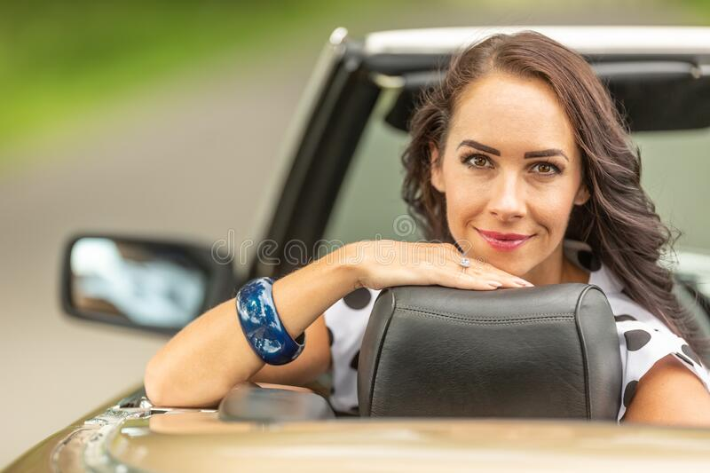 Smiling good looking girl sits behind the driving wheel of a cabriolet, turned backwards royalty free stock photography