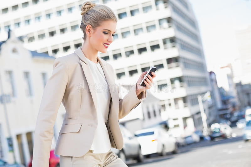 Smiling gorgeous businesswoman text messaging stock photography