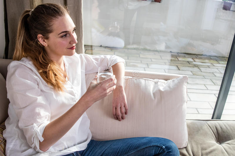 Smiling gorgeous girl daydreaming with glass of water at home royalty free stock images