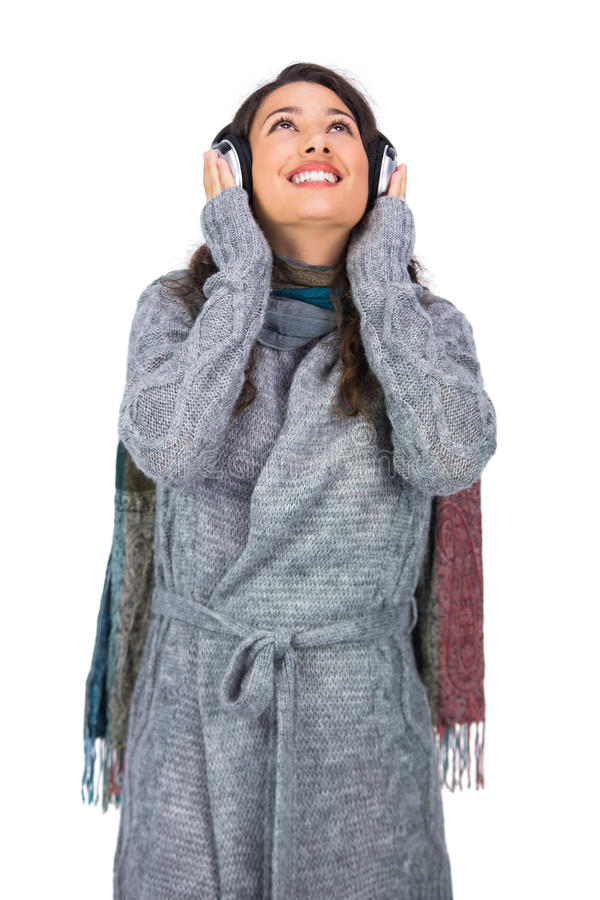 Smiling gorgeous model wearing winter clothes listening to music stock images