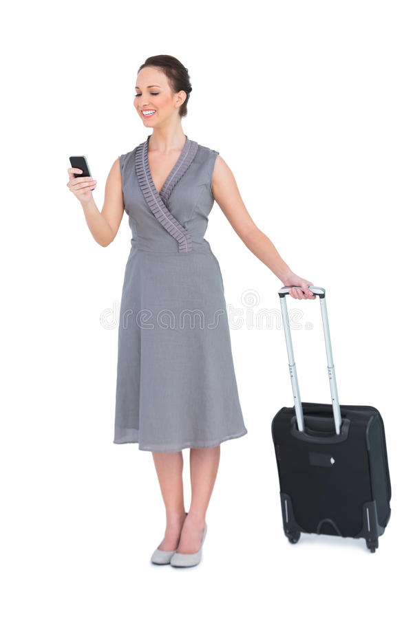 Smiling gorgeous woman with her suitcase texting royalty free stock photo