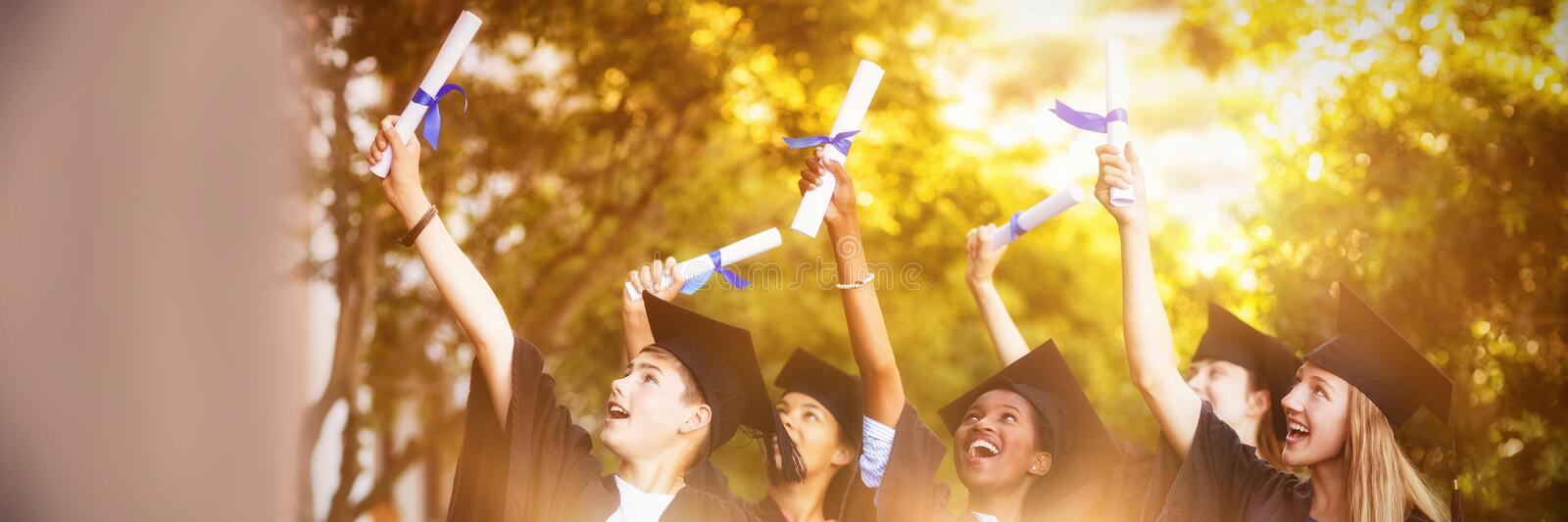 Smiling graduate school kids standing with degree scroll in campus stock photos