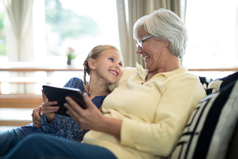 Download Smiling Granddaughter And Grandmother Using Digital Tablet On Sofa Stock Photo - Image of casual, hair: 97396746