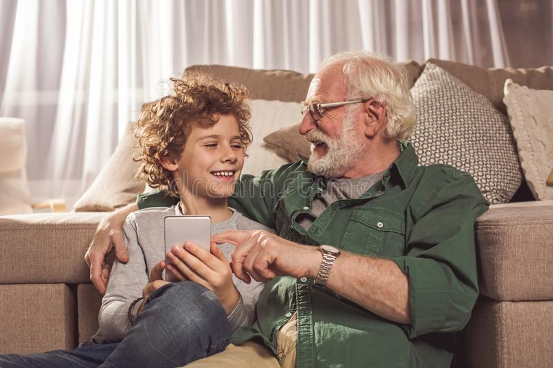Smiling grandfather and child keeping phone stock images