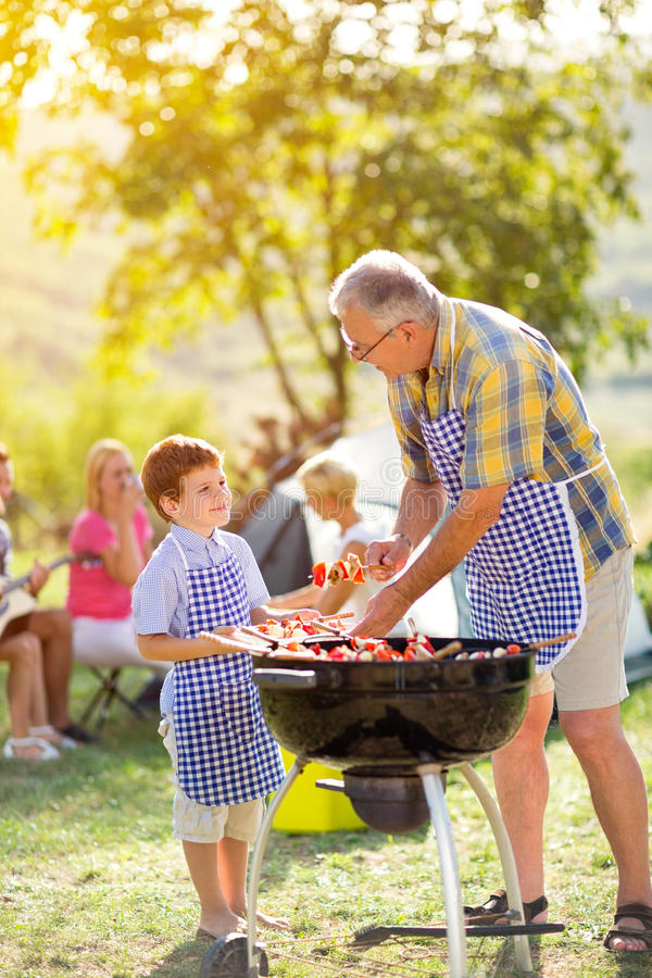 Smiling grandfather and grandson at barbecue stock photo