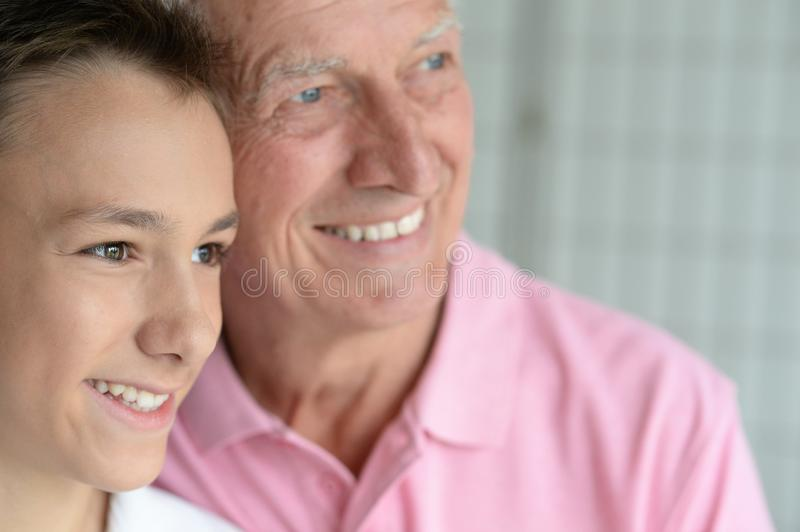 Smiling grandfather and grandson. Portrait of smiling grandfather and his teen grandson royalty free stock photography