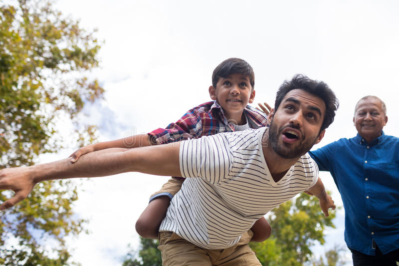 Smiling grandfather looking at man giving piggy backing to son. Smiling grandfather looking at men giving piggy backing to son with arms oustretched in yard royalty free stock images