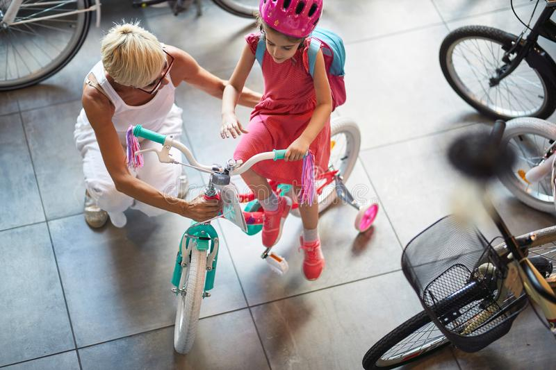 Smiling grandmother and child shopping bicycle and helmets in bike shop. Smiling grandmother and cute child shopping bicycle and helmets in bike shop royalty free stock photos