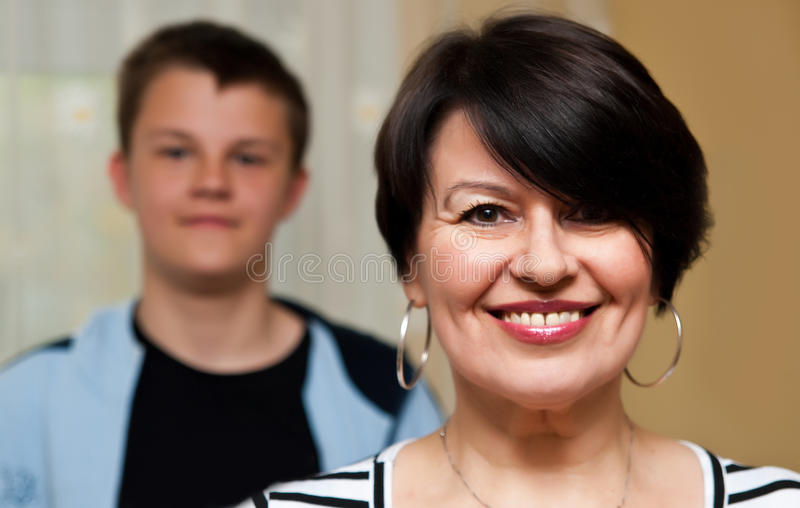 Smiling grandmother with grandson. A portrait of a smiling grndmother, with her grandson in the backdrop stock photo