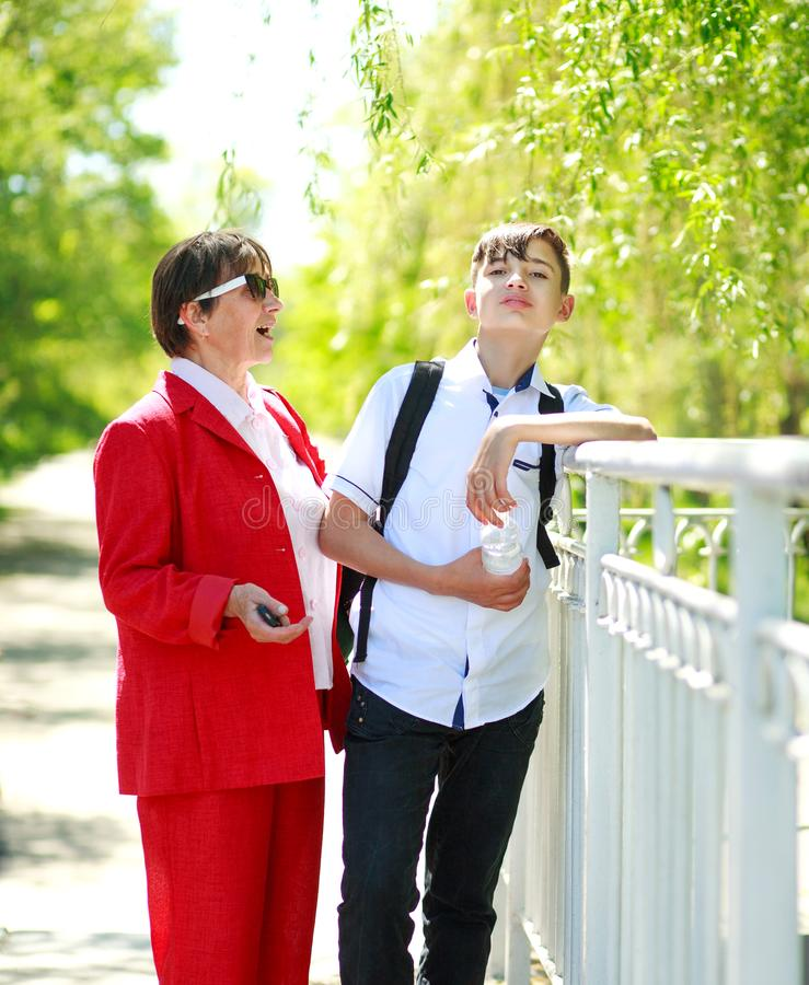 Smiling grandmother and grandson relax and talking together. Happy smiling grandmother and grandson relax and talking together in the summer city park royalty free stock photo