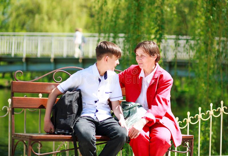 Smiling grandmother and grandson relax and talking together. Happy smiling grandmother and grandson relax and talking together in the summer city park stock images