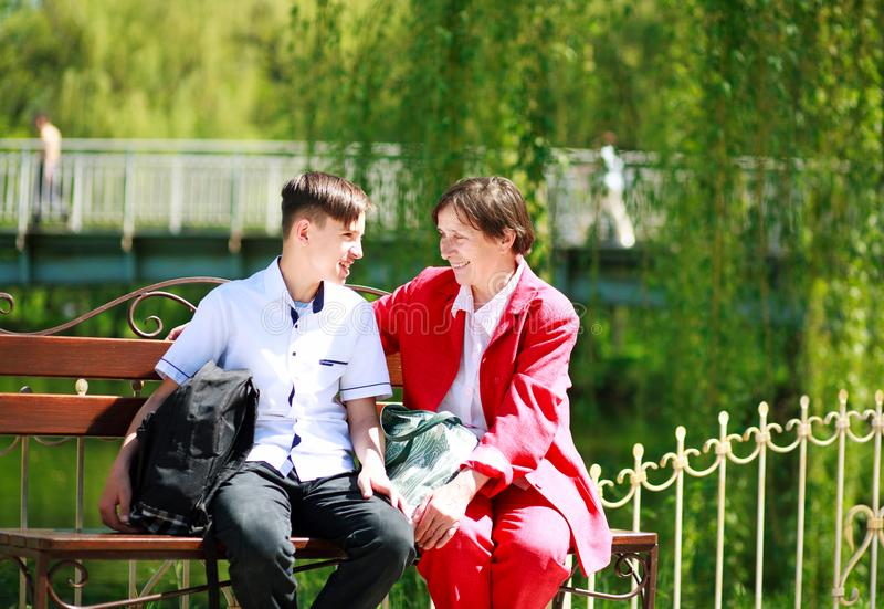 Smiling grandmother and grandson relax and talking together. Happy smiling grandmother and grandson relax and talking together in the summer city park stock image