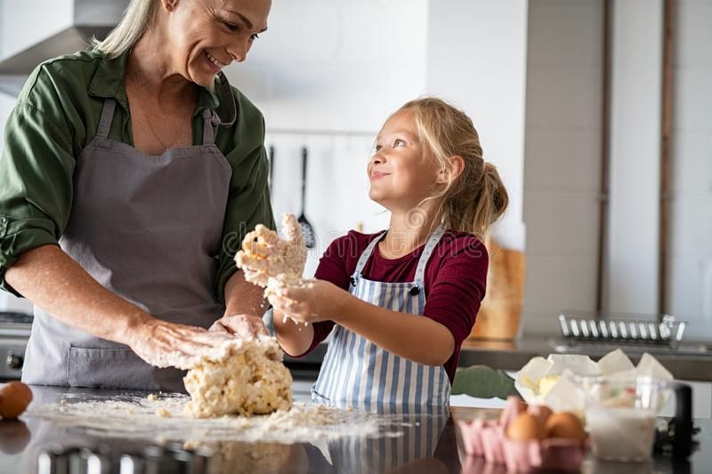 Smiling grandmother and happy child kneading dough stock photography