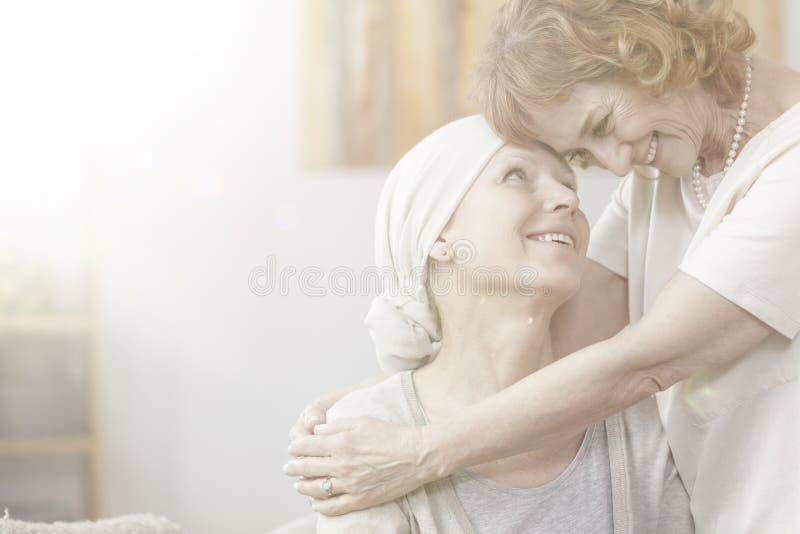Smiling grandmother hugging sick woman royalty free stock image