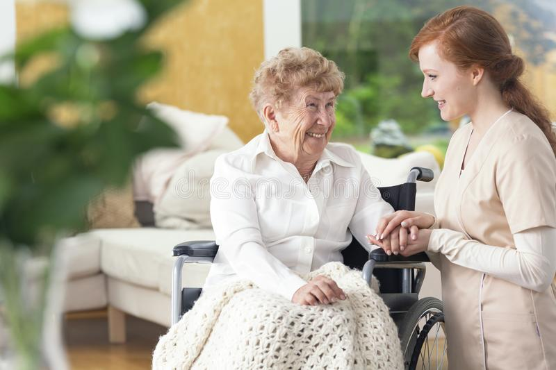 Smiling grandmother in a wheelchair and a friendly nurse talking. And laughing royalty free stock photography