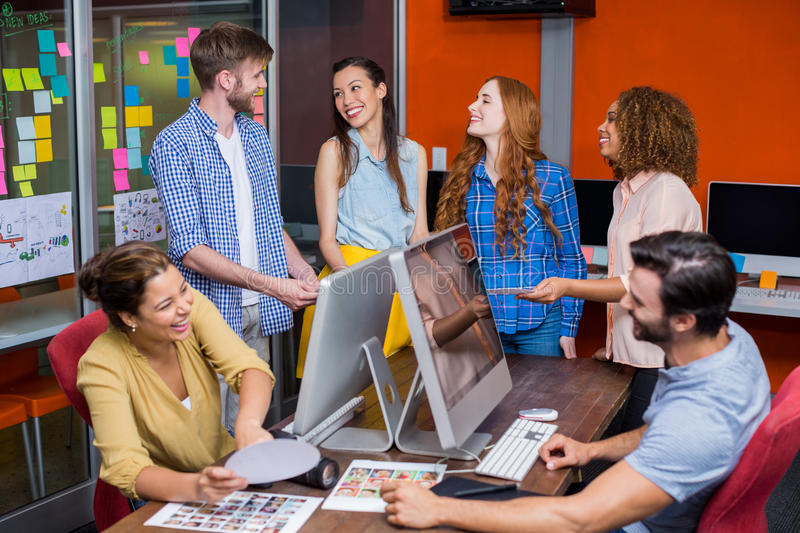 Smiling graphic designers interacting with each other while working at desk royalty free stock photography