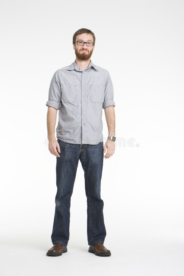 Smiling with gray shirt. Man with beard standing full length inside a white photo studio with gray shirt rolled up and denim jeans. He has smile on his face and royalty free stock images