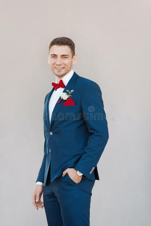 Smiling Groom agaist gray wall. Portait of a young happy handsome man in suite. Gorgeous guy on gray background stock image