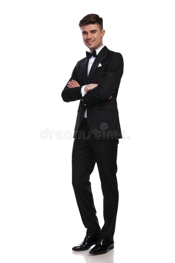 Smiling groom in black tuxedo standing with arms folded. Smiling groom in black tuxedo standing on white background with arms folded, full body picture royalty free stock photography